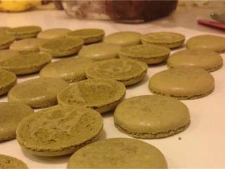 抹茶红豆夹心马卡龙,把马卡龙放在烤箱的最底层, 烤制11分钟, 拿出后放在烤架上冷却. 把尺寸相近的放在一起.