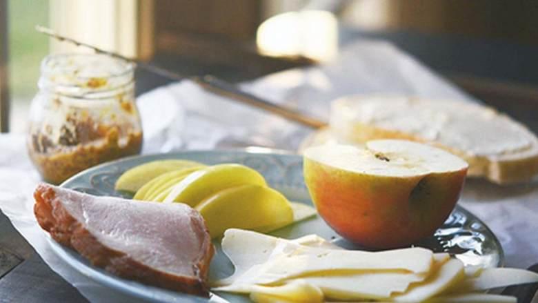 苹果火鸡三明治,用中低火加热煎锅,将一片面包放入加热好的锅中,涂上黄油的一面朝下。在朝上的一面面包上涂上一半的法式芥末籽酱。