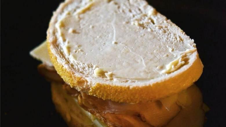 苹果火鸡三明治,在没涂黄油的那面面包上涂上法式芥末籽酱。将面包放在三明治上,黄油面朝上。