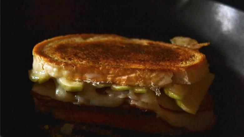 苹果火鸡三明治,用中低火煎三明治直到面包变成金黄色,芝士开始融化。大约每面煎5-8分,如果面包变色太快,需要降低温度。