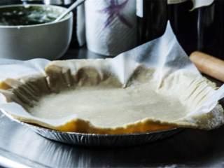 草莓奶冻派,烤箱预热到180度。在厨房案板上撒一层面粉,用擀面杖把面团慢慢擀成3毫米厚的圆饼。