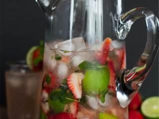 草莓莫吉托,把混合物倒进大水罐里,加入冰块、苏打水、白朗姆酒,再搅拌均匀。