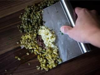 香辣欧芹酱牛排,凤尾鱼片(3)沥干后拍干。 柑刺山花蕾(4 茶匙)也沥干。然后剁碎绿橄榄(3), 大蒜瓣,柑刺山花蕾和凤尾鱼片。 然后都倒入之前的碗中。