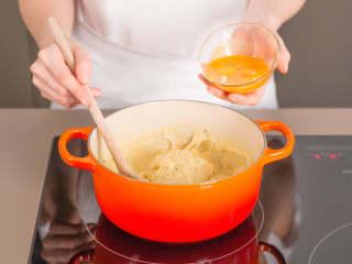 炸牛奶,在另一个平底锅中融化黄油。加入面粉,中小火加热2分钟,搅拌混合。从第一个锅中拿出香草豆荚和肉桂棒,往面粉混合物中加入牛奶。微沸5分钟,持续搅拌,直至混合物变稠。拌入蛋黄,然后关火取下平底锅。