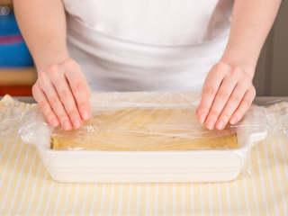 炸牛奶,在烤盘上铺好塑料膜。倒入面糊,抹匀顶部,铺上更多塑料膜。冷藏4小时或隔夜,直至黄油凝固。