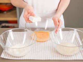 炸牛奶,将面粉、搅打好的鸡蛋和面包屑分别放到一个搅拌碗中。将牛奶块先沾取面粉,然后蛋液,最后粘上面包屑。