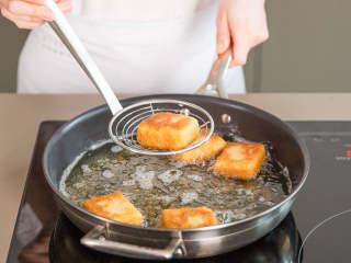 炸牛奶,在大煎锅中,中火热油。将粘好面包屑的牛奶块每面煎2分钟,直至变成金棕色。放到铺好厨房用纸的盘子中,稍微吸掉油分。