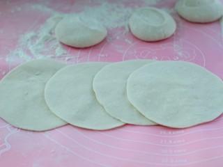 东北猪肉酸菜馅包子,再用擀面杖擀成中间厚些、边缘薄些的饼皮