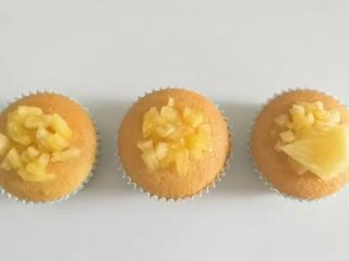 果味长崎纸杯蛋糕,最后把凤梨果肉丁和果肉片取适量放在蛋糕上,摆上薄荷叶装饰即成!