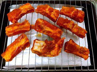 好吃到吮手指的新奥尔良烤排骨,腌制好的排骨摆在烤架上,下面用锡纸放在烤盘里接住,以免弄脏烤箱不好清理。