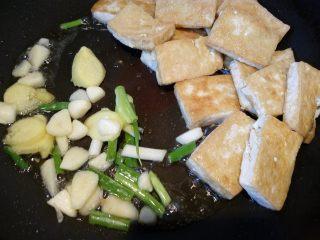菌茹烩豆腐,把豆腐推到一边,倒入葱姜蒜等调料。
