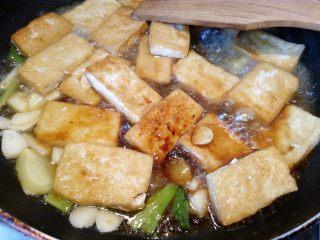 菌茹烩豆腐,倒入半碗高汤,大火烧开,加入一小勺盐,小火焖煮5分钟让豆腐入味。