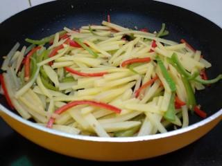 醋溜土豆丝,倒入土豆丝翻炒均匀。