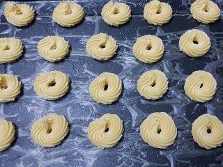 #曲奇菜谱秀# 奶香曲奇(淡奶油版),黑上烤盘上铺层油纸、接着挤第二盘