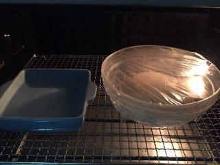 蛋黄千层酥,揉好的面团盖保鲜膜密封放温暖湿润处醒发,我是放到了烤箱里,没有调温度,因为烤箱比较封闭,旁边放了一碗温水。