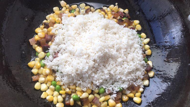 土豆腊肉焖饭,玉米粒,豌豆翻炒大概2分钟,添加大米一起翻炒。