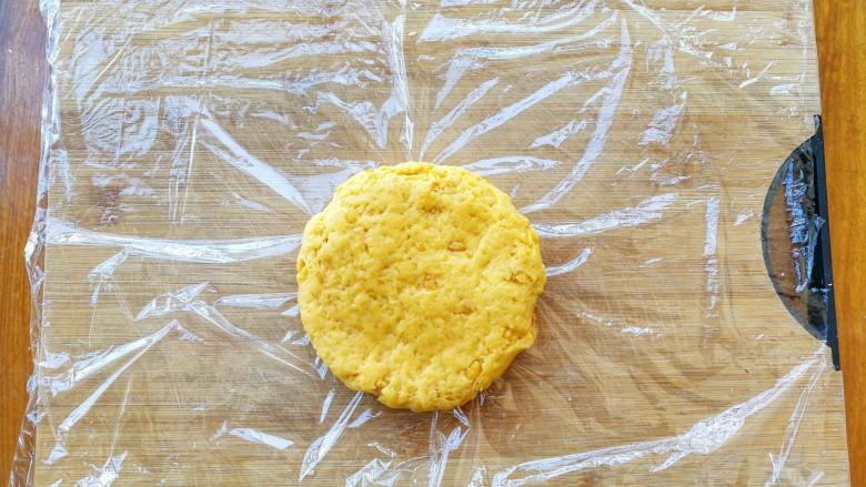 两种造型的红薯芝麻饼干,酥脆香甜有营养~,案板上铺上保鲜膜,把红薯面团放中间,压扁,