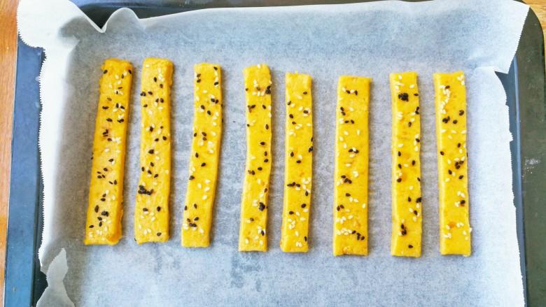 两种造型的红薯芝麻饼干,酥脆香甜有营养~,预热烤箱180°度,烤盘铺上油纸,饼子切成长条,放在油纸上,