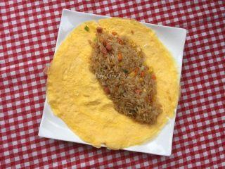 蛋包饭,将炒饭放置蛋皮的一半位置,注意边缘位置留空,用勺子轻压实