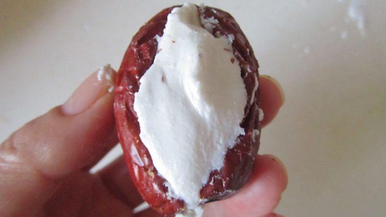 桂花红枣蒸南瓜,拿出1小团糯米粉填入红枣中央;