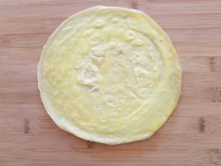 菠萝蛋包饭,平底锅小火加热,锅里抹薄油倒入蛋液,转去动锅使蛋液均匀铺满锅底煎成圆形蛋饼,表面凝固后盛出,不用翻面。
