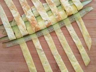 菠萝蛋包饭,把鸡蛋条和黄瓜条按照编花篮的方法编成蛋饼,如图每隔一个把鸡蛋条揭起放入黄瓜条。看到揭开蛋条贴着锅底的颜色了吧,这就是为什么煎蛋饼时不要翻面,要保证表面颜色漂亮,翻面贴到锅底就会有斑纹。