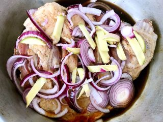 烤羊腿,调味料均匀的涂抹在羊腿上将切好的圆葱和姜摆入羊腿中盖上保鲜膜放入冰箱冷藏25小时煨制入味