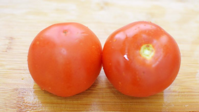 番茄炒蛋,番茄洗净去蒂。下面把番茄去皮,以免影响口感。