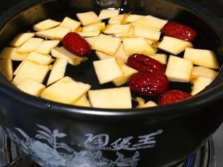 南瓜红枣小米粥,锅里坐水放入南瓜,红枣