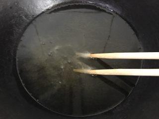 秘制酥鱼,放入筷子试试油温,筷子冒泡就可以入锅炸了,