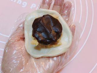 酥得掉渣的蛋黄酥,擀卷好的面团,两头捏到一起,擀成圆片,包好豆沙肉松球,如图用右手食指抵住,面皮朝上,左手大拇指食指用力,用虎口将面皮收紧,全部完成。