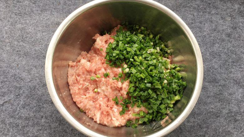韭菜蒸饺子,韭菜段倒入猪肉糜中。