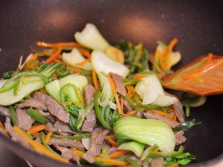 牛肉炒乌冬面,混合翻炒至菜叶变软。