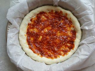 鸡肉海鲜披萨,15.用勺子将酱料涂满披萨底。