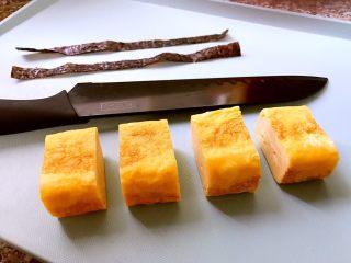 日式厚蛋烧,等蛋卷凉了以后再用刀切成块,这样不容易切坏。剪几条海苔条,用来包裹切好的厚蛋烧