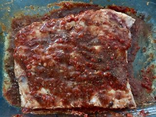 猕猴桃烤猪小排,取出腌好的肉放入预热175度的烤箱中层烤半小时后取出翻面,把盘中酱料均匀抹在排骨上,再次入烤箱半小时。