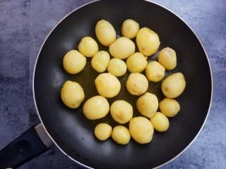 蒜香味的孜然香辣小土豆,取平底不粘锅,锅里入油,放入去皮的小土豆