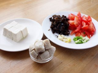 吃豆腐+番茄鱼丸豆腐汤,2.豆腐切方块,木耳随意切几刀,番茄切小块,葱蒜切碎,鱼丸切成小块。