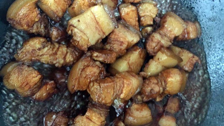 笋干焖五花肉,倒入五花肉翻炒至糖色。