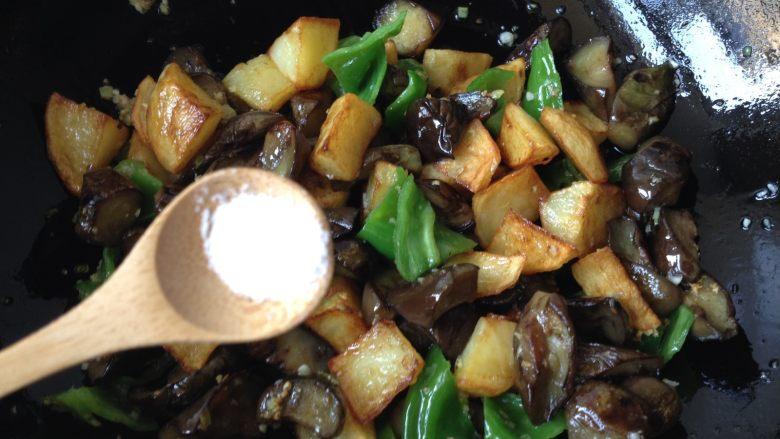 地三鲜,倒入土豆和茄子,再放入适量盐炒匀