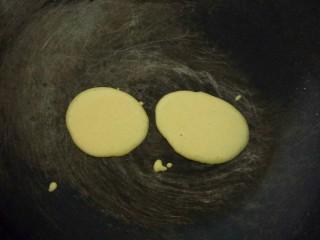 牛奶雞蛋玉米餅,平底鍋微熱,用勺子舀一勺面糊垂直倒入,輕輕晃動鍋使面糊呈圓形,小火煎?