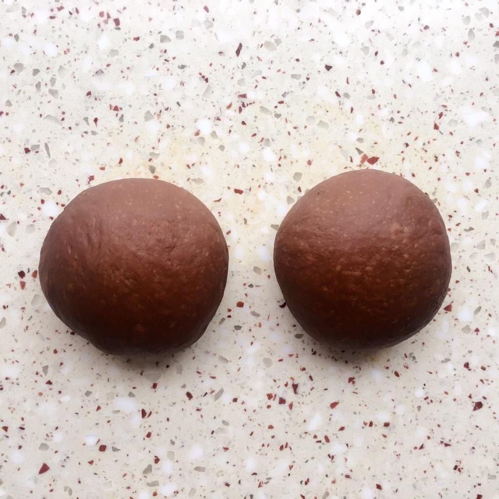 可可麻薯软欧包,面团排气分成2等份</p> <p>盖保鲜膜静置松弛15分钟