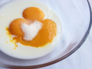 红糖红枣戚风蛋糕,蛋黄里加入牛奶和少量白糖,搅打均匀;