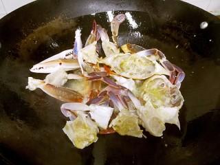 姜葱炒花蟹,把花蟹倒入油锅,暂不翻动。
