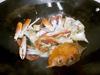 姜葱炒花蟹,约30秒后翻动花蟹,每翻动一次就静置一会儿,让花蟹处于半炸半煎半炒的状态。