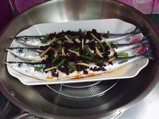 豆豉辣酱蒸秋刀鱼,抹匀后再撒些葱姜丝、放入锅中加水加盖