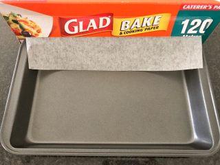 三文鱼奶酪菠菜蛋卷,烤箱预热180度,我们再来准备烤盘,在烤盘上面铺盖一张烤纸,
