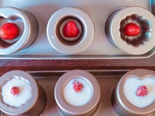 草莓奶冻可可蛋糕杯,把吉利丁粉倒入牛奶里融化,再加热后倒入六连蛋糕模具里,中间加入草莓, 冰箱冷藏至凝固