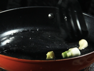 酱烧螃蟹,放入葱段、蒜粒、姜过油翻炒30秒后捞出