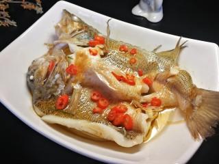 千张鲈鱼,小米椒切小圈,摆放在鱼身上,然后锅内油烧冒烟,趁佩服均匀倒在鱼身上,激发出香味。
